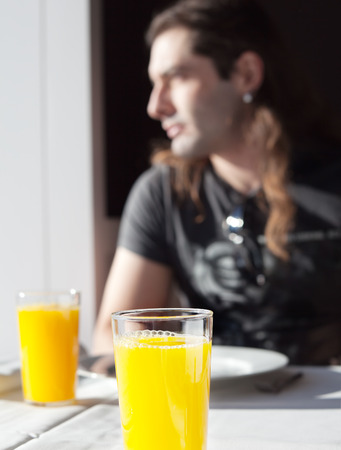 Boy having breakfast glass of orange juice in the light of a window Standard-Bild