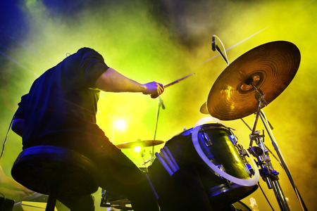 boy playing the drums. Live concert and stage lights.Live concert musician playing drums on stage with lights
