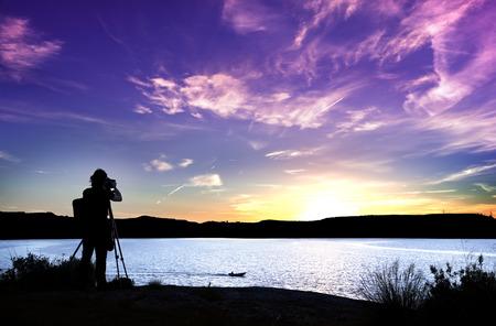 日没時に彼の装置を持つカメラマンのシルエット