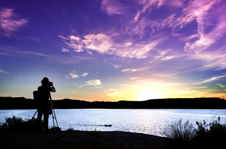 Silhouette of photographer with his equipment during sunset photo