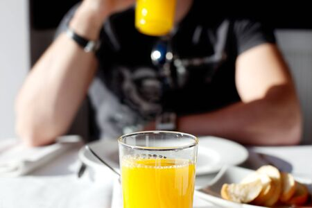 Boy taking a glass of juice in the light of a window
