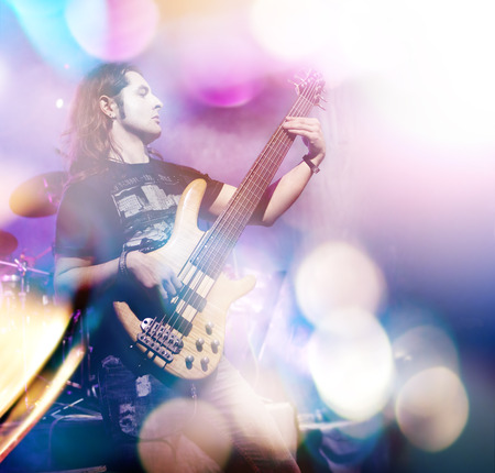 live action: Man playing bass guitar in live concert sequence. Live music with stage lights. Double exposure