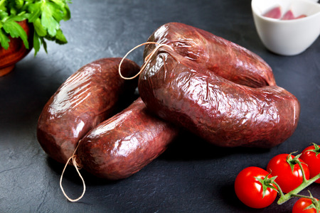 Uncooked fresh blood sausage with parsley and tomato. raw pork ready to cook black stone background
