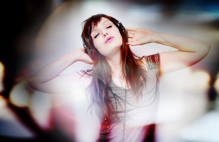 Beautiful young woman listening to music with headphones and singing on neutral background. Lifestyle 写真素材