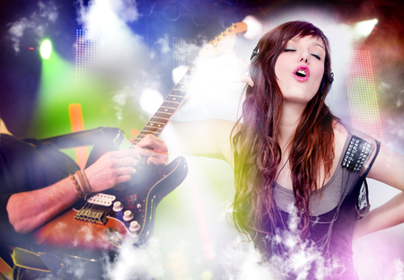 beautiful woman listening to music with headphones and singing. Live music background with guitar and bright lights on stage. Live music and party concept.