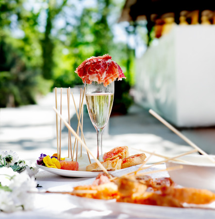 Outdoor catering. Food events and celebrations. Sliced ham and toast with champagne Standard-Bild