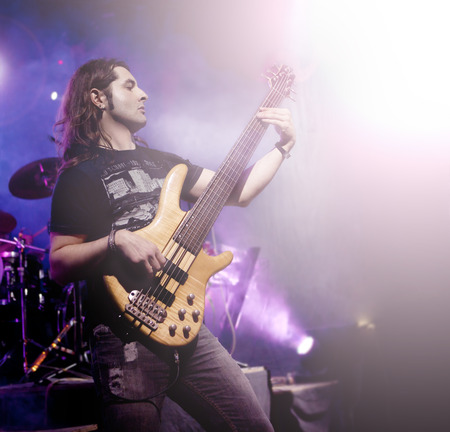 Man playing bass guitar in live concert sequence. Live music background Standard-Bild