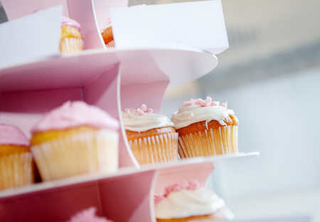 Desserts and sweets for parties. sweets for celebrations. Pink cupcakes with whipped cream and chocolate cupcake stand in.