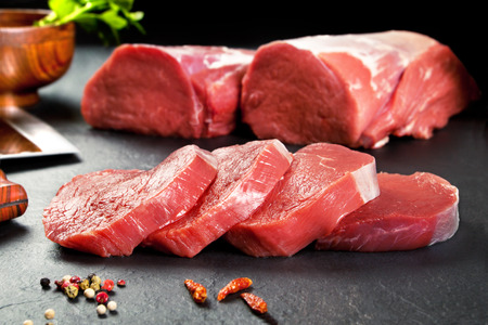 loin: Fresh and raw meat. Sirloin medallions steaks in a row ready to cook. Background black blackboard Stock Photo