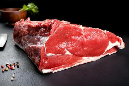 carne cruda: Carne fresca y cruda. Chuletón. Pieza entera fresca de carne en el fondo negro pizarra