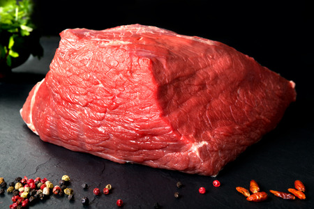 Pork uncooked fresh beef and veal. Fresh red meat spiced black stone background Standard-Bild