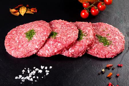 carnes rojas: Carne. Carne cruda. filete de hamburguesa en fondo negro con las hierbas y el tomate Foto de archivo