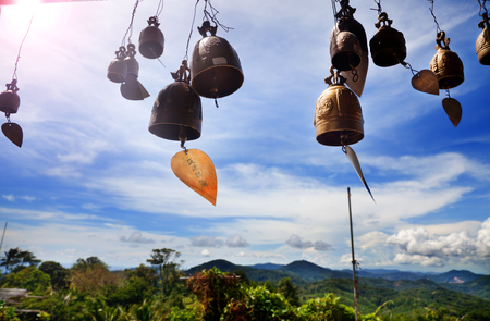 Row of golden bells in buddhist temple. Background of mountains in Asia, Thailand