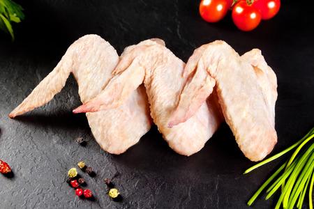 新鮮な生の肉。翼鶏肉を調理する準備ができています。背景黒い黒板 写真素材