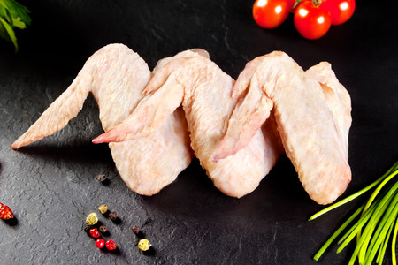 Fresh and raw meat. Chicken wings white ready to cook. Background black blackboard Standard-Bild