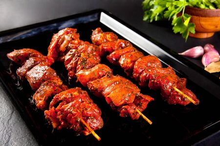 Pork skewers on the grill and barbecue. Still life on black background. BBQ meat