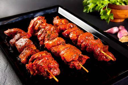 Varkensvleesspiesjes op de grill en barbecue. Stilleven op zwarte achtergrond. BBQ vlees
