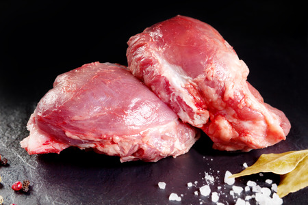Fresh and raw meat. Cheeks, red pork ready to cook on the grill or barbecue. Black slate background Standard-Bild
