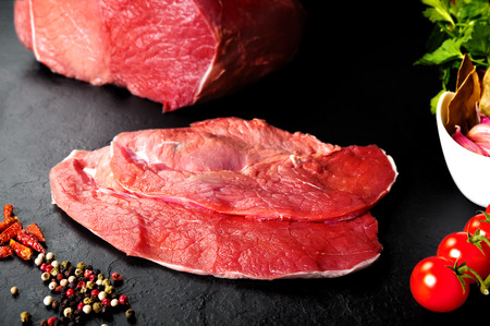 Fresh and raw meat. Still life of steaks ready for cooking. Black slate background. Meat carnage.