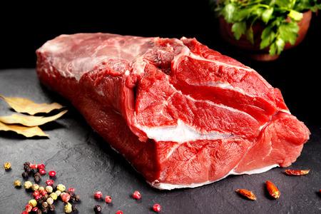 Carne fresca y cruda. Todavía la vida de la carne roja listo para cocinar en la barbacoa. Fondo de pizarra Negro