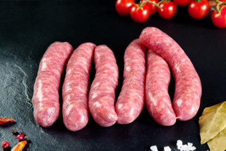 原料と新鮮な肉。新鮮なソーセージと鶏肉を調理する準備ができています。黒いスレートの背景。肉屋の肉。