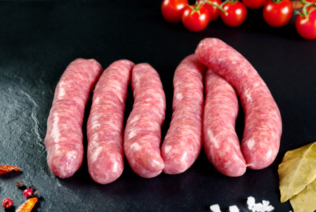 carnicero: La carne cruda y fresca. Salchichas frescas y la carne de pollo listo para cocinar. pizarra de fondo negro. carne de carnicería.