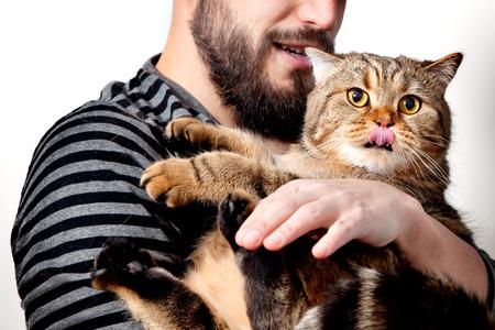 男は、白い背景の上の彼の美しい猫を抱いてします。人と動物