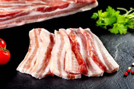 Fresh and raw meat. Still life of bacon BBQ steaks. black slate background Archivio Fotografico
