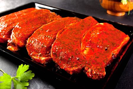 fillets marinated pork loin ready to cook. Loin steaks tray on Black background with parsley
