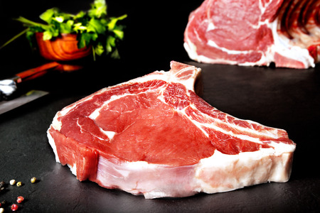 meat on grill: Fresh and raw meat. Ribeye. Uncooked steaks grilled BBQ on black background blackboard. Grilled meat and barbecue, steaks uncooked meat. BBQ Stock Photo