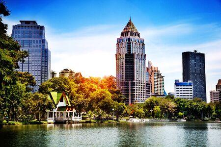 Landschaft im Lumpini Park in Bangkok, Thailand. See, Sonnenuntergang Hintergrund und moderne Wolkenkratzer in der Stadt Standard-Bild - 61506361