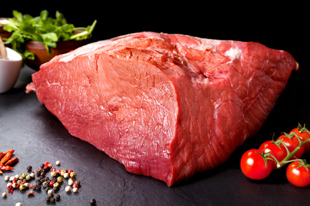 Fresh and raw meat. Still life of red meat steak ready to cook on the barbecue. Black slate background