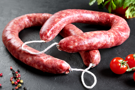 white meat: Raw and fresh meat. Fresh sausages and chicken meat ready to cook.  Black slate background Stock Photo