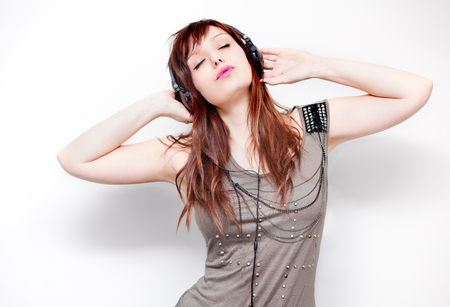 Beautiful young woman listening to music with headphones and singing on neutral background. Lifestyle Standard-Bild