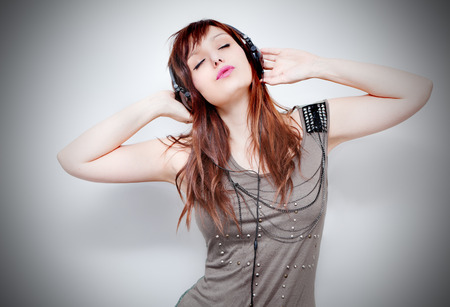 Beautiful young woman listening to music with headphones and singing on neutral background. Lifestyle Standard-Bild - 118815893