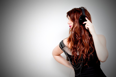 Beautiful young woman listening to music with headphones and singing on neutral background. Lifestyle Standard-Bild - 118815897