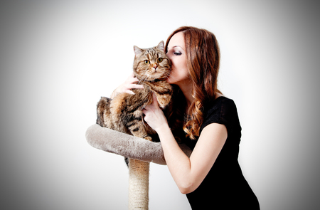 Beautiful girl kissing her cat on white background. People and pets Standard-Bild - 118816010
