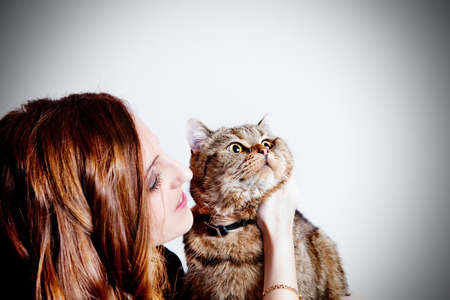 Beautiful girl with her cat on white background. People and pets 写真素材