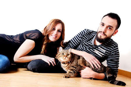 Young couple with their cat at home.Animals, lifestyle