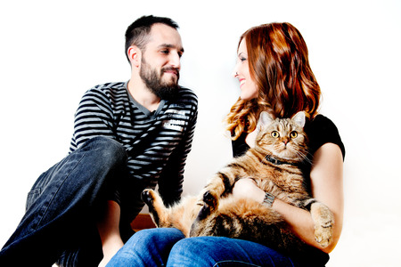 Young couple with their cat at home. Lifestyle