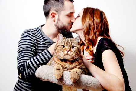 Young couple with their cat at home.Domestic animals Standard-Bild - 118816022