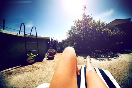 Legs of woman sunbathing with garden and pool in background