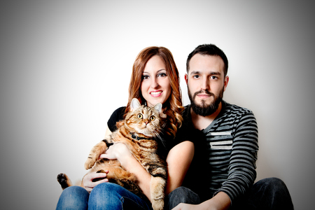 Young couple with their cat at home Couple, pets. 写真素材