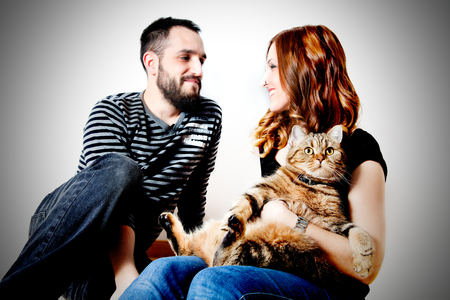 Young couple with their cat at home Couple, pets.LIFESTILE