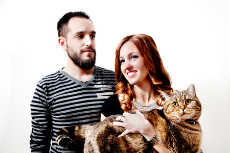Young couple with their cat at home Couple, pets. animals