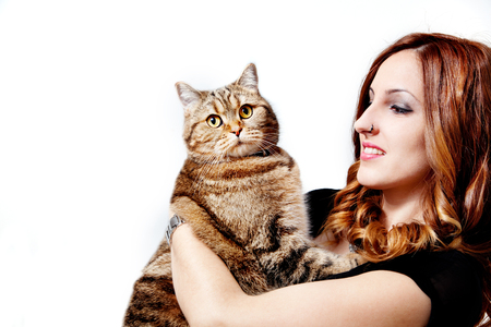 Beautiful girl with her cat on white background.Lifestyle Standard-Bild