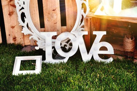 The word love composed of white letters on the sunset. Decoration proposal. Planning of wedding, celebrations in exterior.