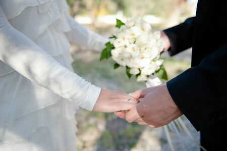 Closeup of a wedding couple holding hands, wearing a wedding ring