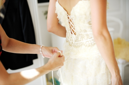 Bridesmaid hands helping the bride to dress for the wedding\ ceremony