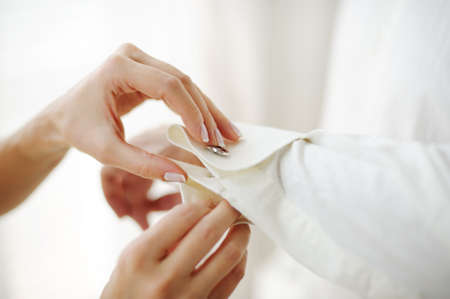 cuff: the hands of the bride buttoning grooms shirt cuff